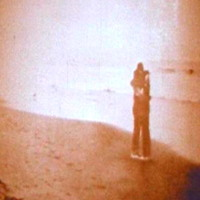 A sepia picture of a couple hug at the boardwalk of a beach