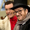 Stephen Colbert is to Elvis Costello as Jon Stewart is to Bruce Springsteen